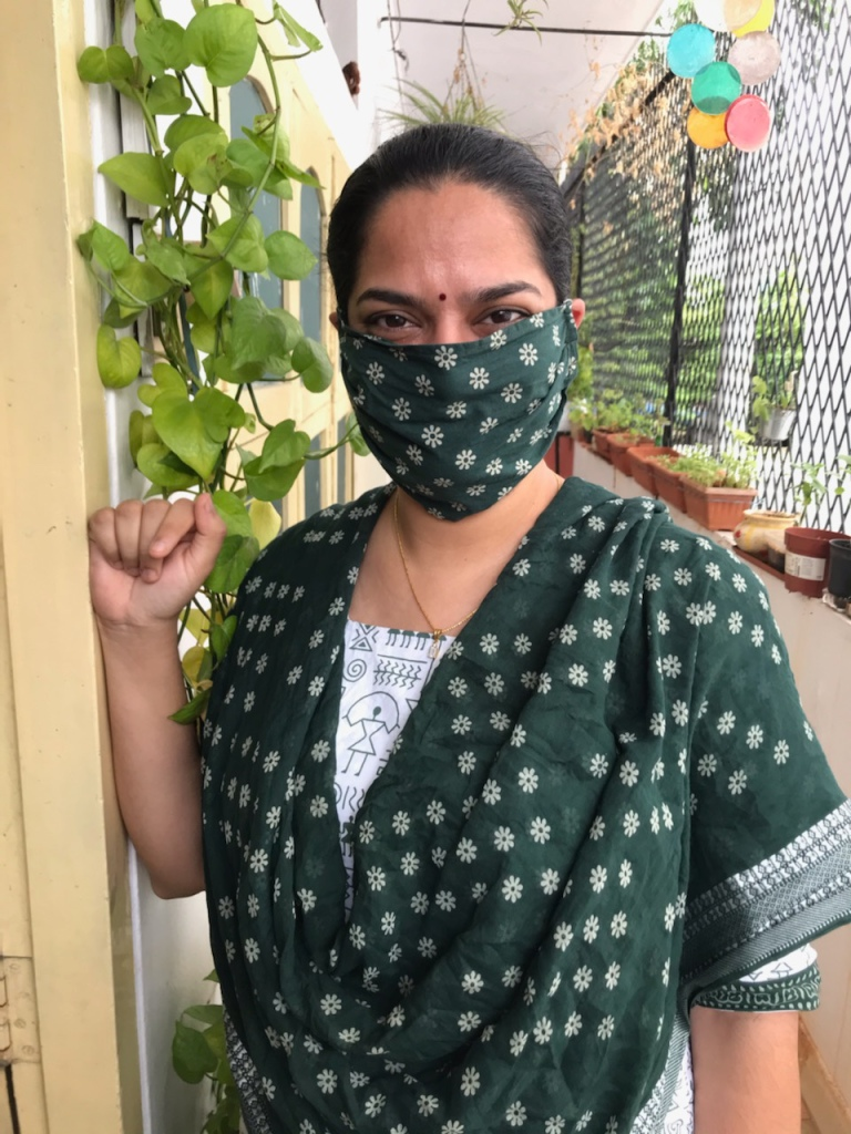 Padmini seen here in a white and green salwar kameez and also wearing a matching face mask. She is  smiling while looking into the camera with a balcony herb garden and  colorful wind chimes in the background